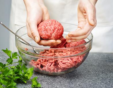 Chef making hamburgers in kitchen with ground beef