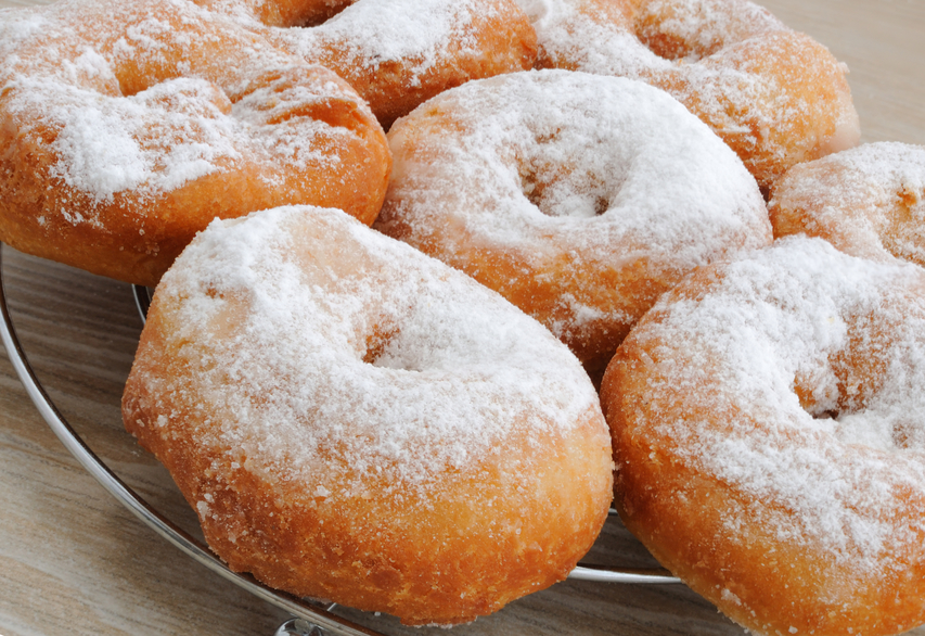 Fried donuts with powdered sugar in a close-up on the stand